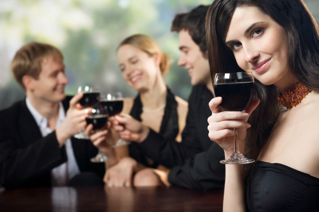 Two young couples with red wine at celebration or party